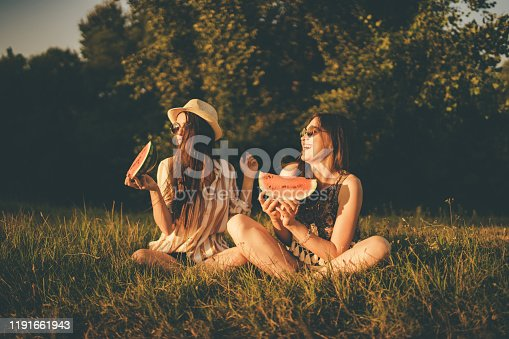 Two young beautiful caucasian women having a watermelon snack in a park.