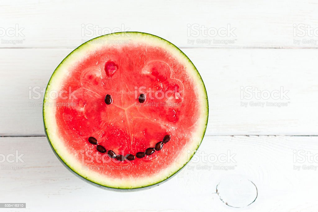 watermelon with smile on white wooden background stock photo