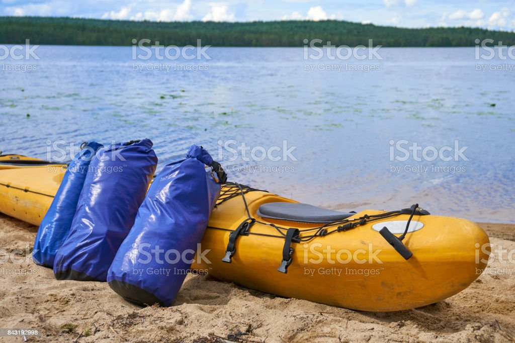 Waterproof bags standing by yellow plastic kayak stock photo