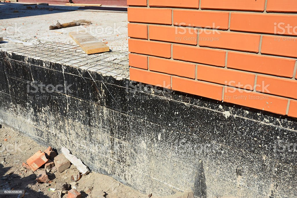 Waterproofing a new brick house foundation with spray on tar stock photo