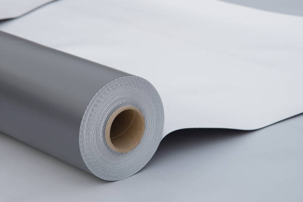Waterproofing and insulation at construction site, opened pvc membrane roll lying on roof closeup. Copy space for your text. Waterproofing and insulation at construction site, opened pvc membrane roll lying on roof closeup. Copy space for your text pvc stock pictures, royalty-free photos & images