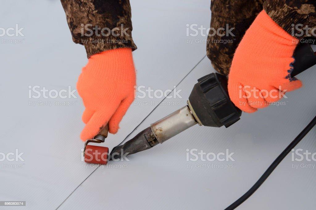 Impermeabilización y aislamiento en el sitio de construcción, techo proceso de sellado de membrana sintética con herramienta de mano de aire caliente. Nueva tecnología de protección. Closeup. - foto de stock