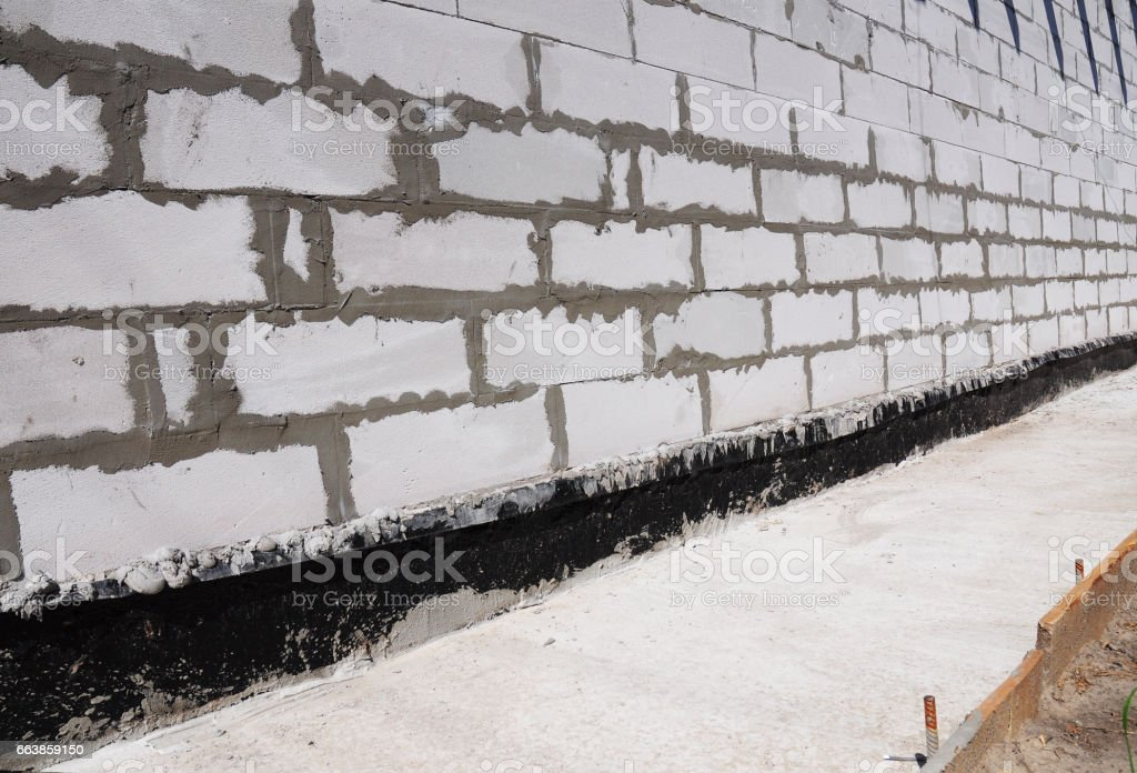 Waterproofing and insulation house  foundation wall. Waterproofing house foundation with bitumen membrane. stock photo
