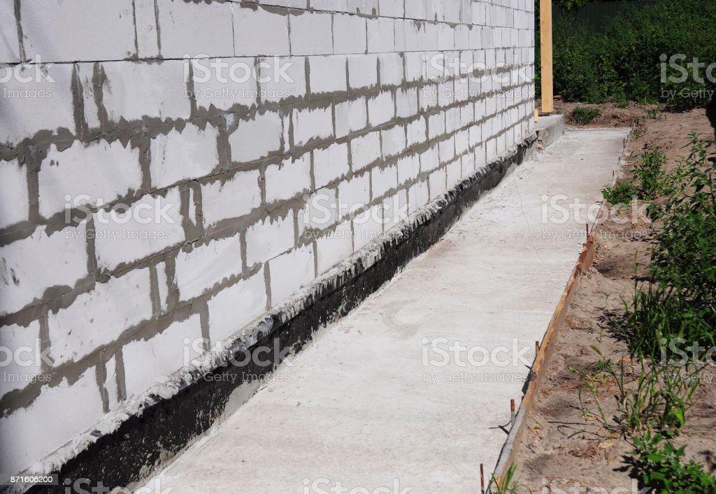 Waterproofing and insulation unfinished house foundation wall. Waterproofing house foundation with bitumen membrane. stock photo