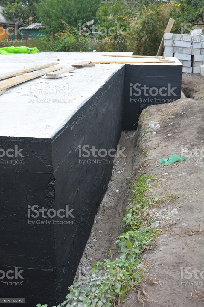 Waterproofing house foundation with bitumen spray on tar stock photo