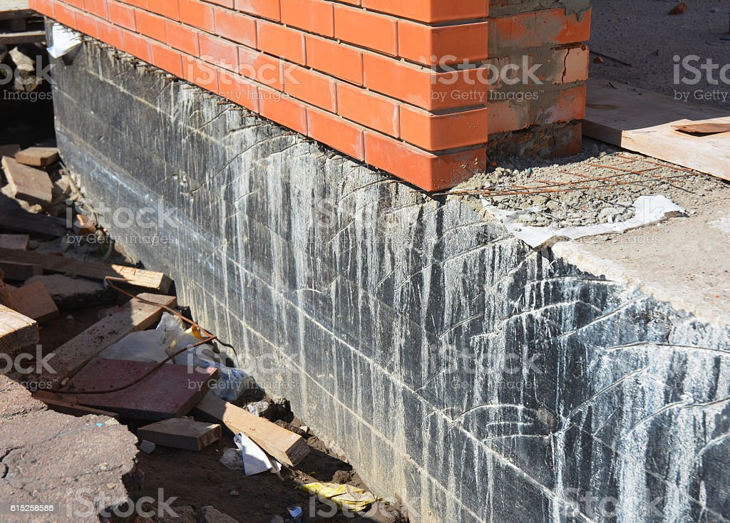 Waterproofing house foundation with spray on tar. stock photo