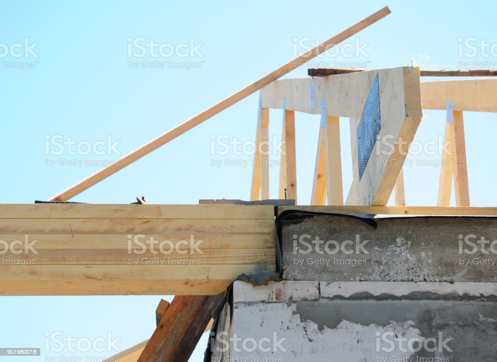 Waterproofing wooden roof truss with bitumen membrane against water. Building house roofing construction. stock photo