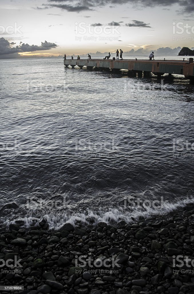 water's edge and pier with people stock photo