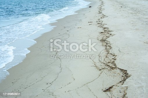 Coastline close at water's edge with wavy lines in sand from sea debris