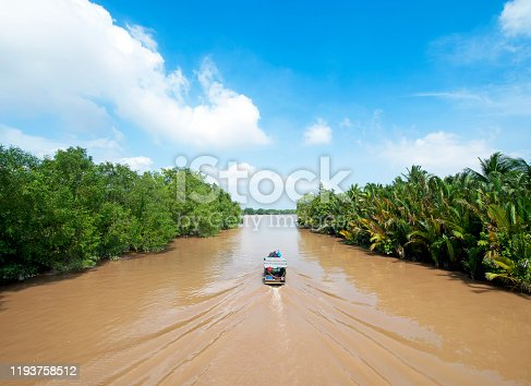 A working boat follows the green slow rippled waters of the wide and sluggish Mekong River - a hub for large communities of industrial and residential development that is the lifeblood or lifeline of the local population as they flow to the Mekong Delta, South Vietnam