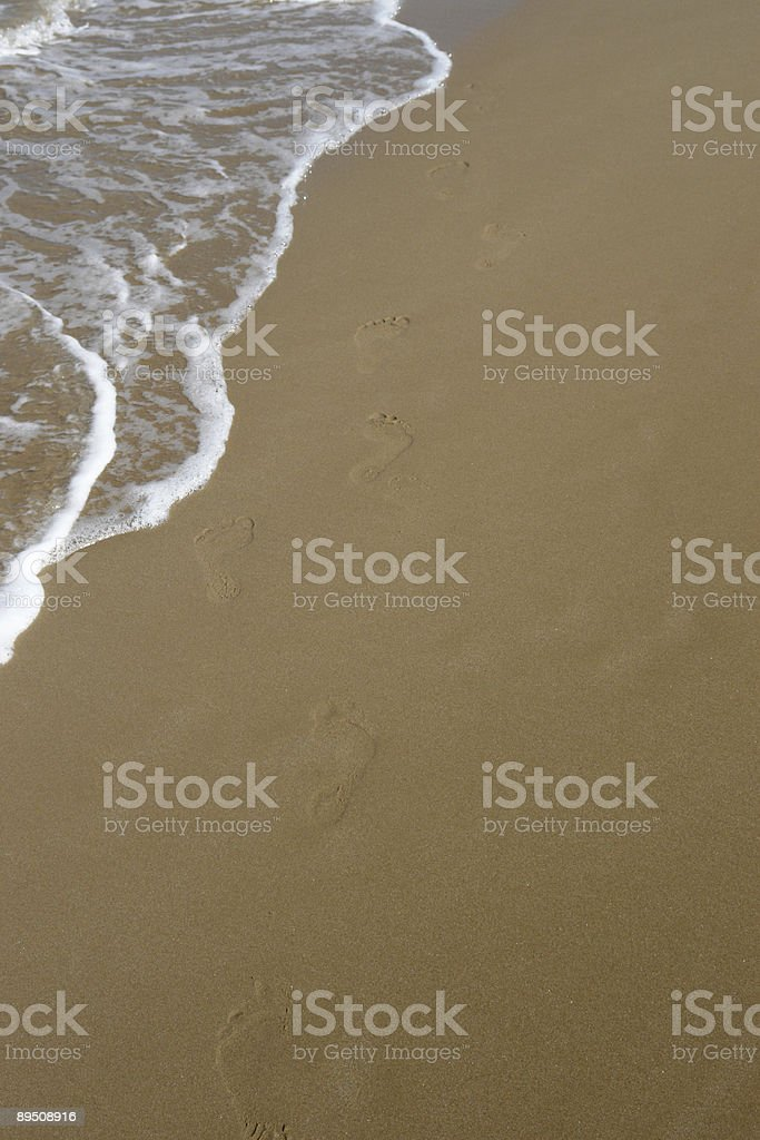 waterside footprints in the sand royalty-free stock photo