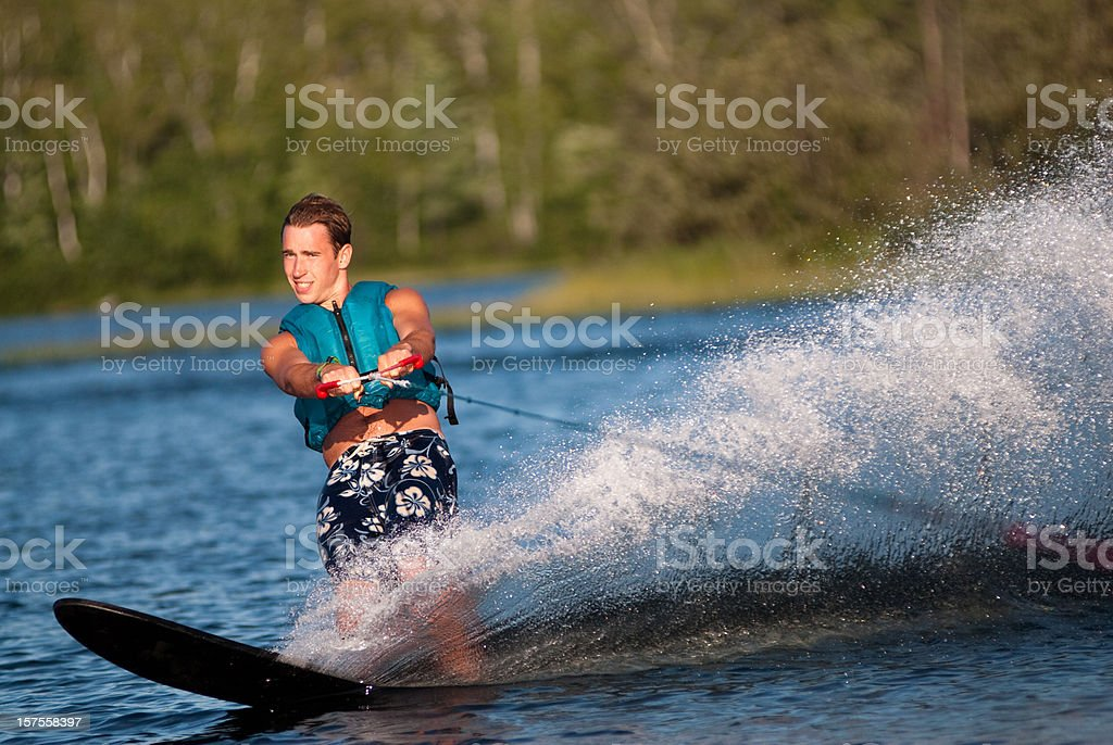 Waterskiing with man shredding waves stock photo