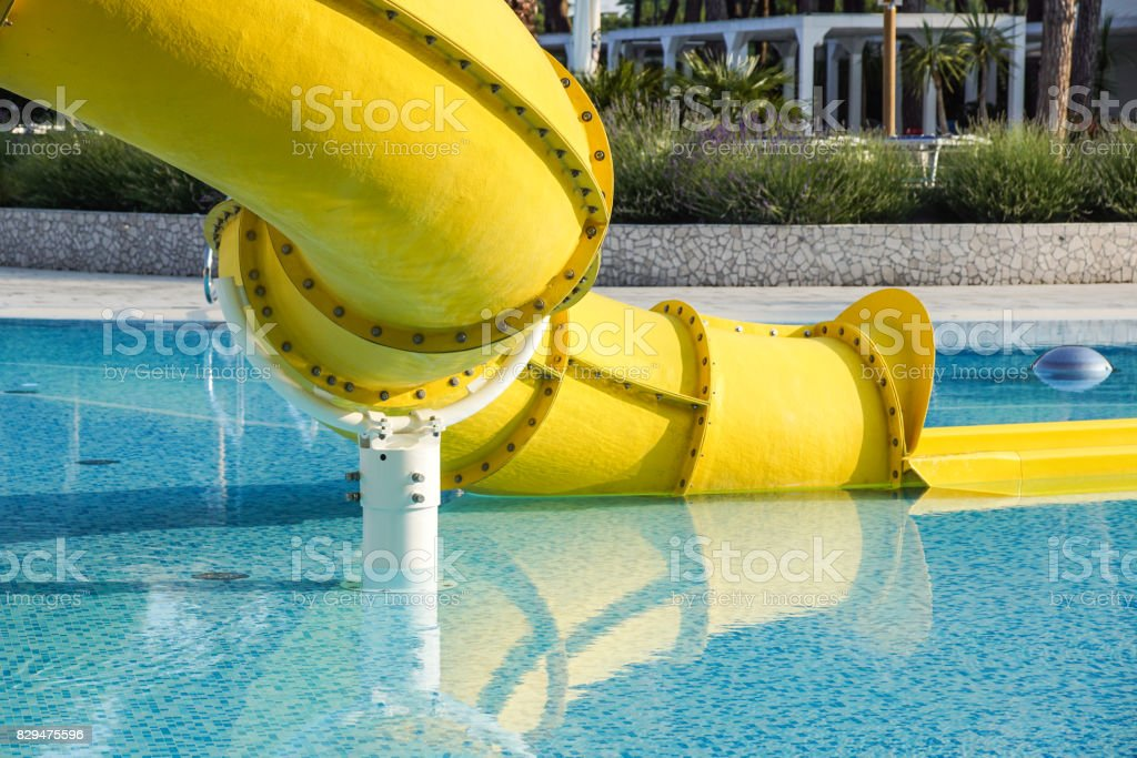 waterslide ending in a swimming pool stock photo
