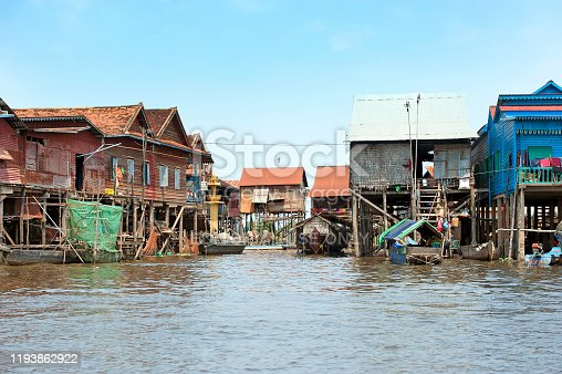 Kompong Khleang floating village, Tonle Sap Lake, Cambodia. A complete and thriving community with travel and transport by boat living in colourful basic ramshackle shacks, homes and houses of wood, timber and tin buildings, standing on stilts or afloat on the rippled water of the lake near Siem Reap, Cambodia