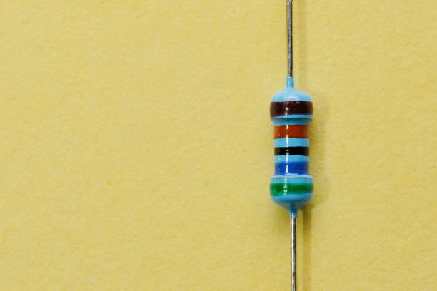 1/4 watt resistor isolated on yellow background stock photo