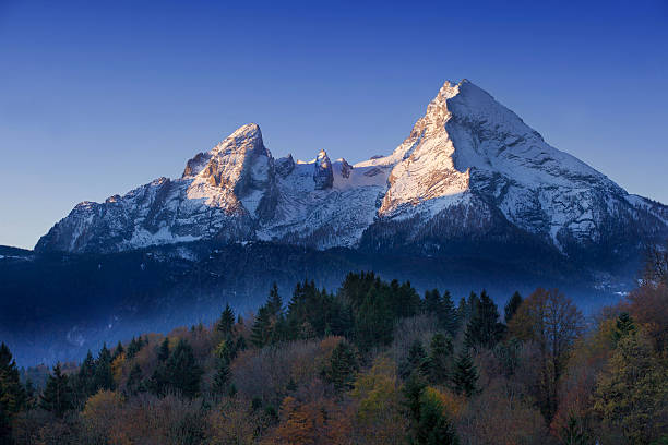 Watzmann at Morning The Watzmann mountain awake in the mornig. Bright blue sky . Fog in the valley. Autumn picture. bavarian alps stock pictures, royalty-free photos & images