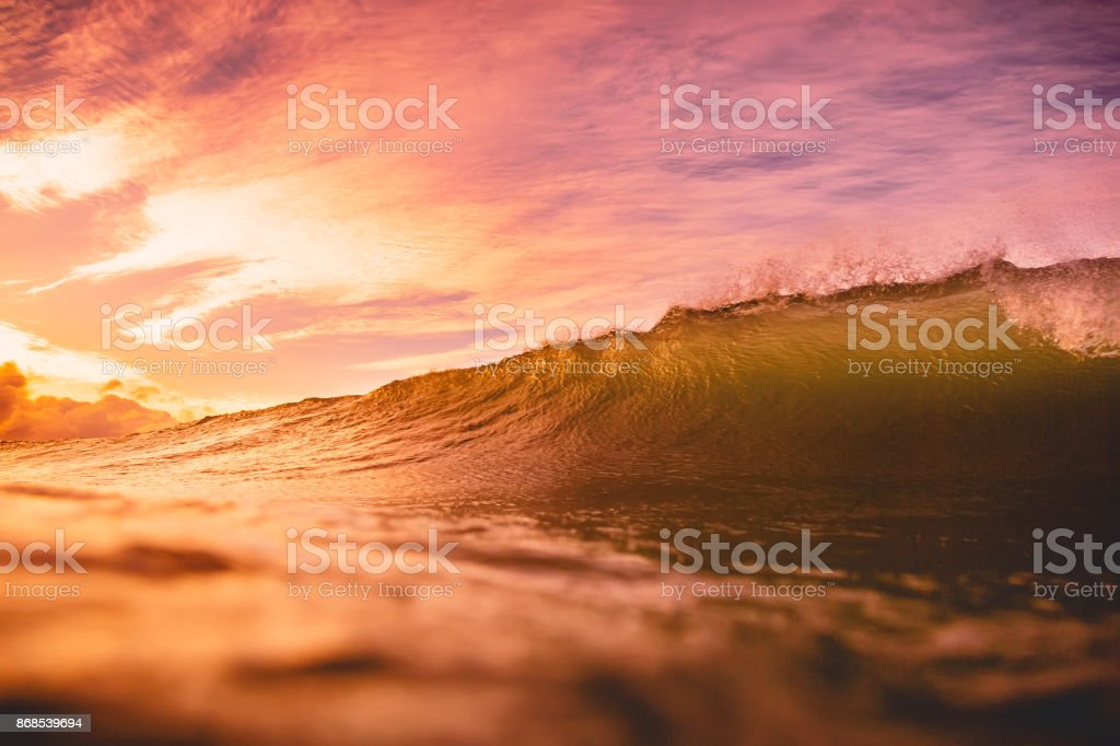 Wave at sunset or sunrise in ocean. Wave and with warm sunset or sunrise colors stock photo