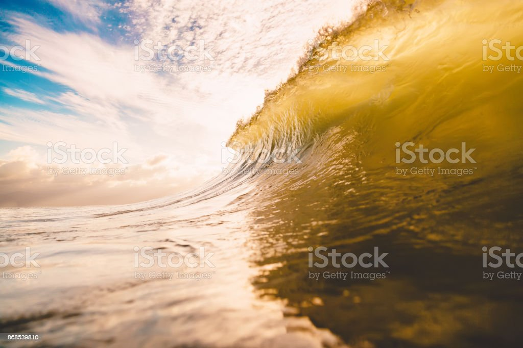 Wave barrel in ocean at sunset or sunrise. Wave crashing at sunrise stock photo