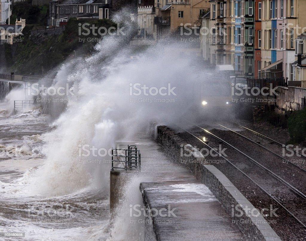 Wave breaking over local train at Dawlish stock photo