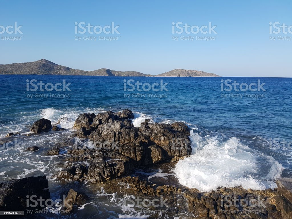 Wave breaking over rocks stock photo