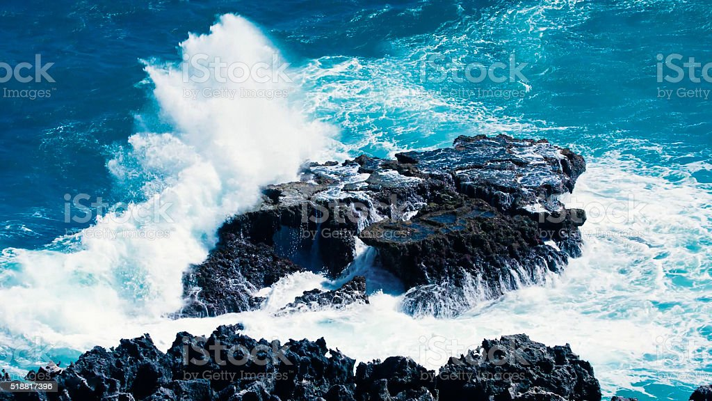 Wave breaks on a rock of a volcanic island. stock photo