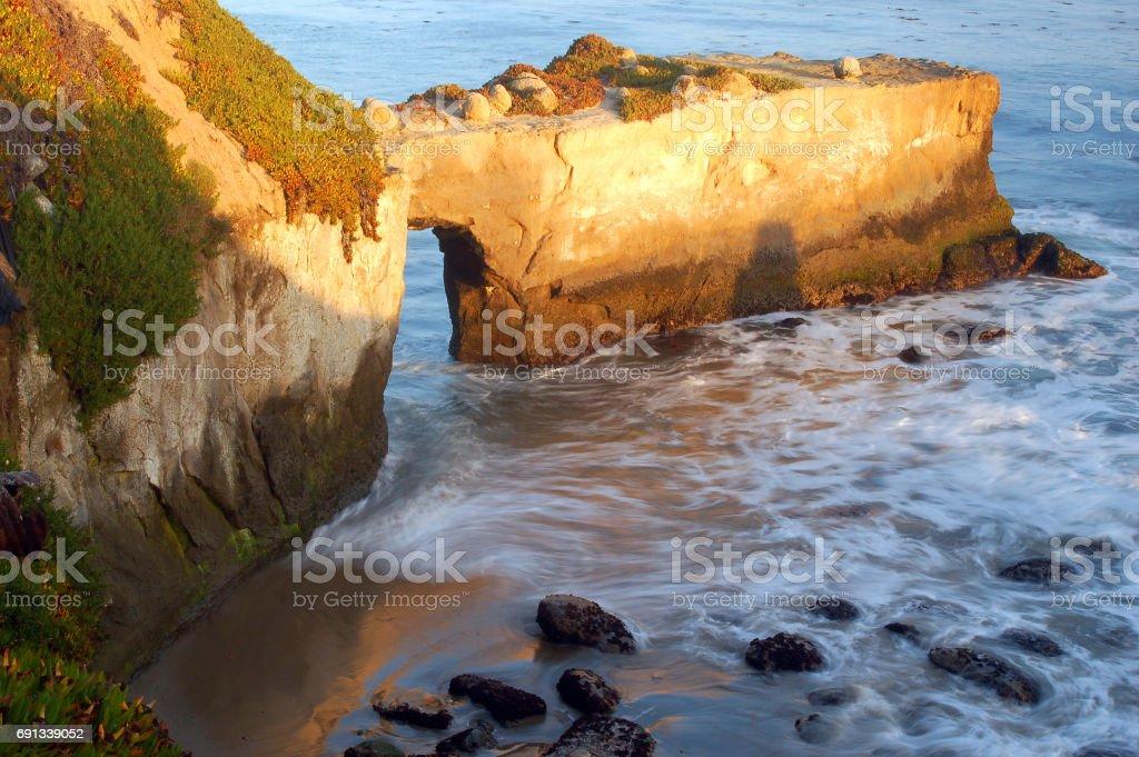 A wave crahes along a rocky shore stock photo