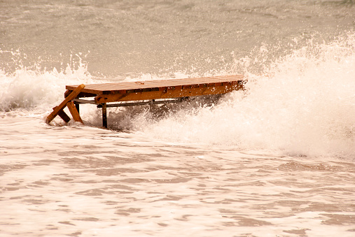 Wave crashes along a wooden jetty