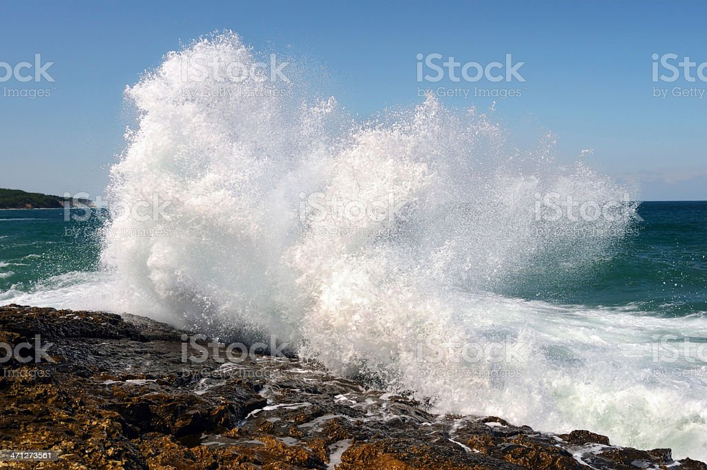 Wave crashing against the beach stock photo