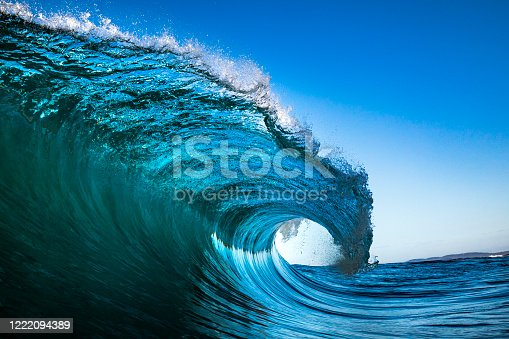 Wave crashing in ocean with blue sky