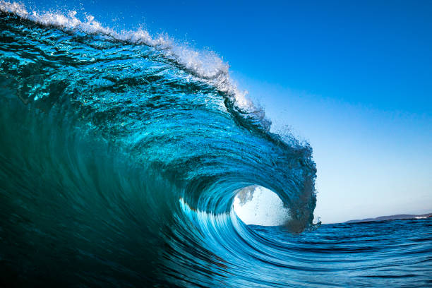 Wave crashing in ocean with blue sky stock photo