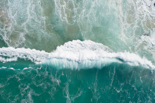 istock Wave crashing in the blue turquoise ocean. Aerial of a rolling strong and powerful wave in the sea at sunrise 1163293138