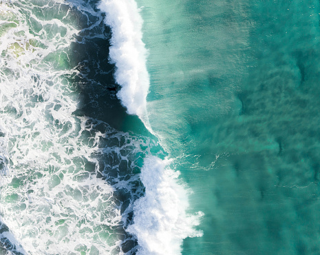istock Wave crashing in the blue turquoise ocean. Aerial of a rolling strong and powerful wave in the sea at sunrise 1163293996