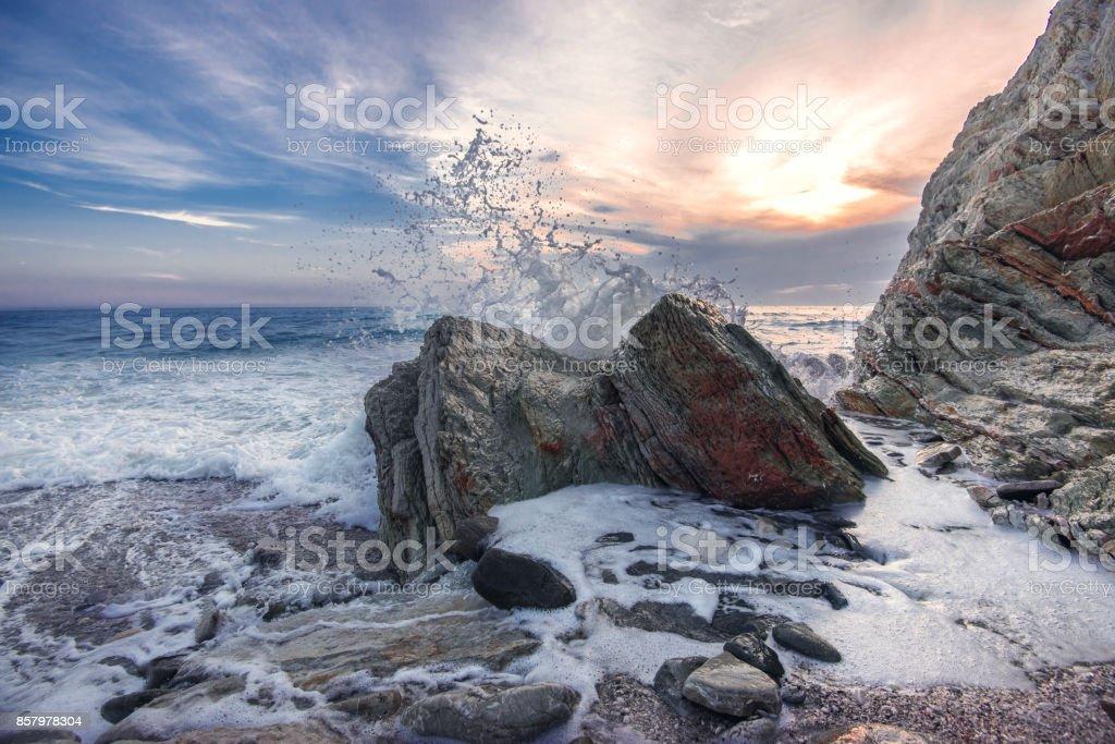 Wave crashing on rocks stock photo