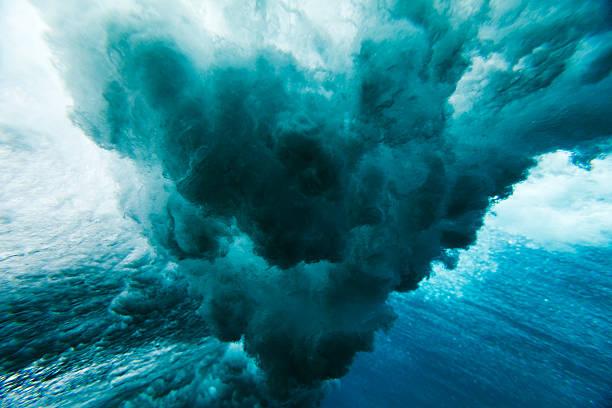Wave crashing underwater stock photo
