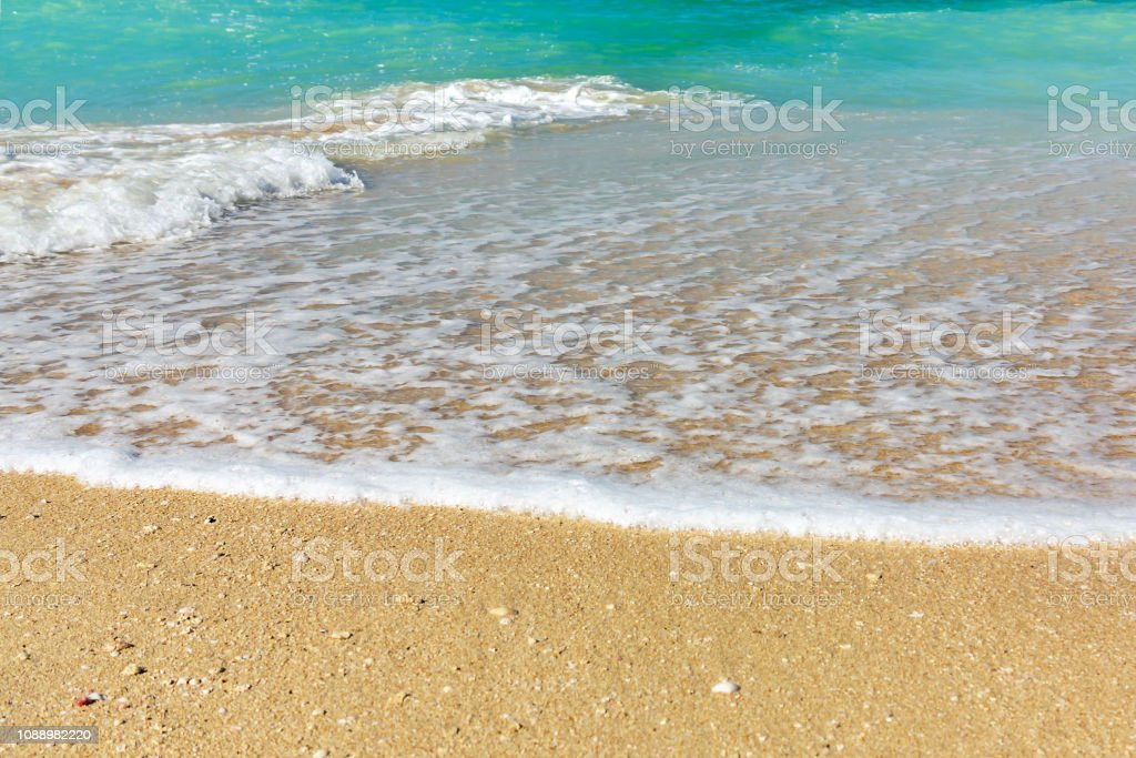 Wave of surf on the sea coast, clean sea shore and turquoise water.