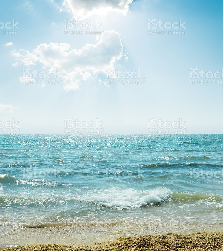 wave on sea and blue sky with clouds and sun stock photo