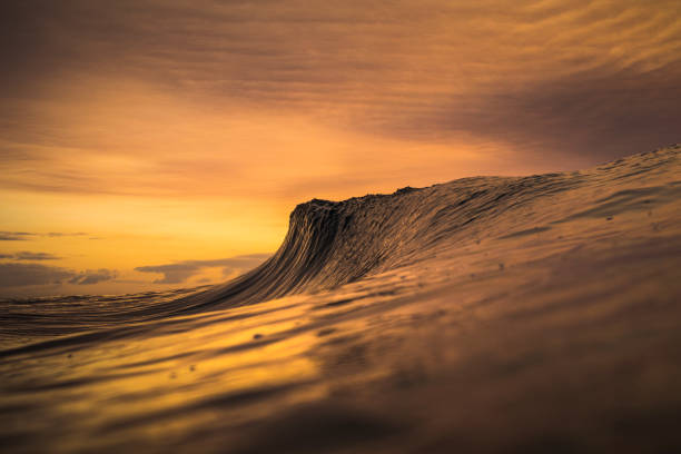 Wave peaking about to break with burnt orange sky from forest fire stock photo