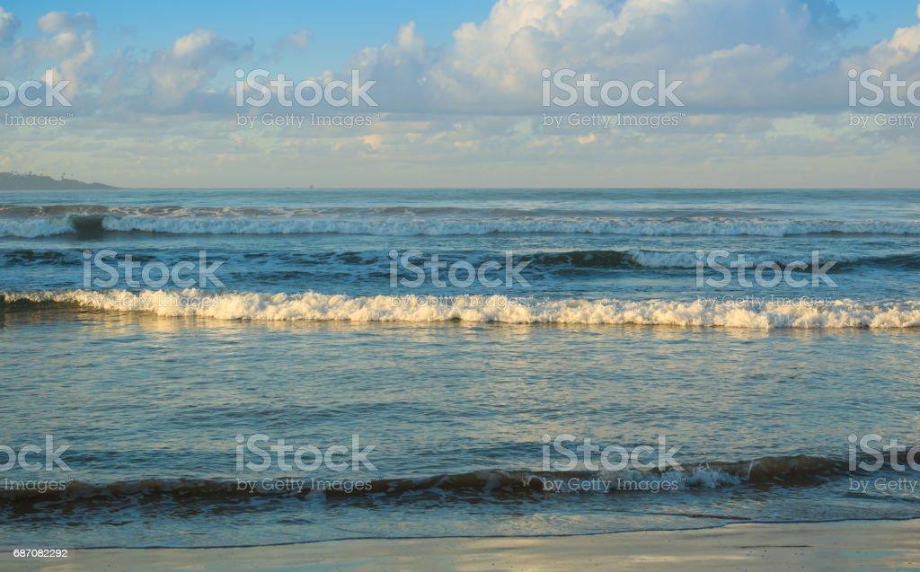 Welle läuft zum Sandstrand unter blauem Himmel Lizenzfreies stock-foto