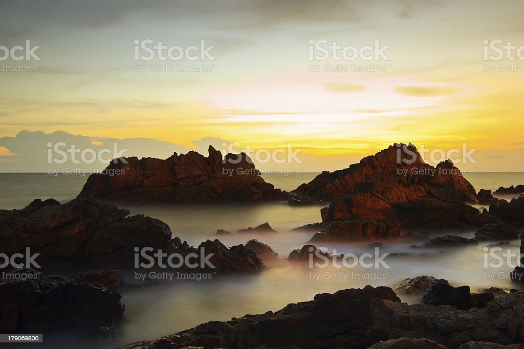 Wave splash on rock in the sunset royalty-free stock photo