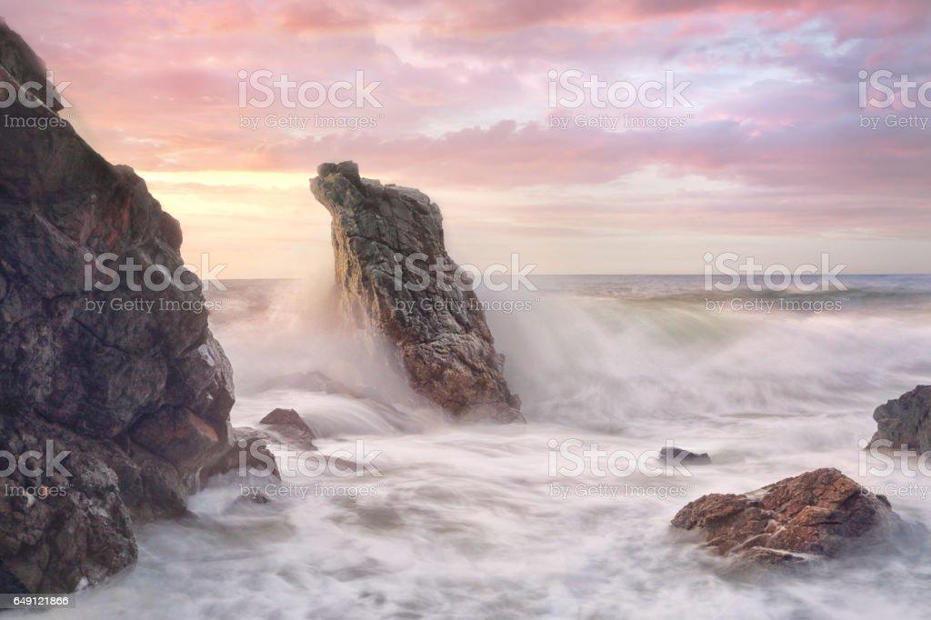 Wave surges through rocky coastline at sunrise stock photo
