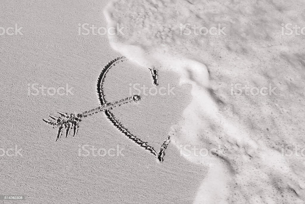 Wave washes over heart in the sand stock photo