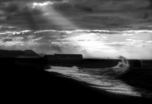 A person stands on the cobb in Lyme Regis as a storm sends large waves crashing onto the shore.
