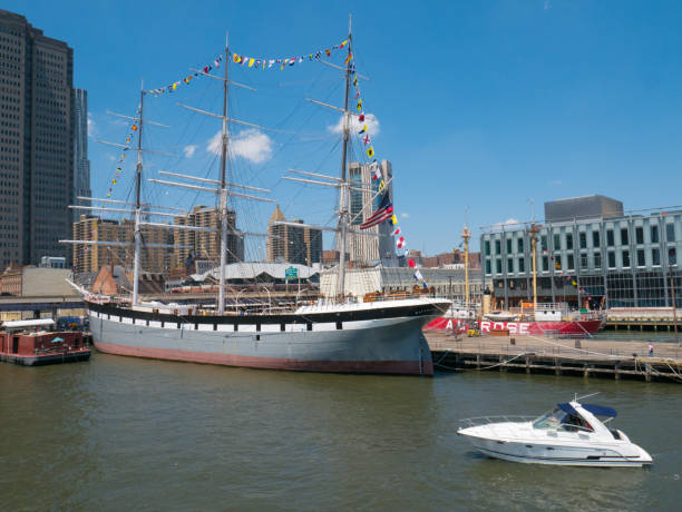 Wavertree sailing ship and a modern motorboat at the South Street Seaport Museum in Manhattan, New York, NY. NEW YORK, NY, USA - JULY 19, 2017: Wavertree iron-hulled sailing ship built in 1885 at the South Street Seaport in Manhattan, New York, NY. The vessel was added to the National Register of Historic Places on June 13, 1978. south street seaport stock pictures, royalty-free photos & images