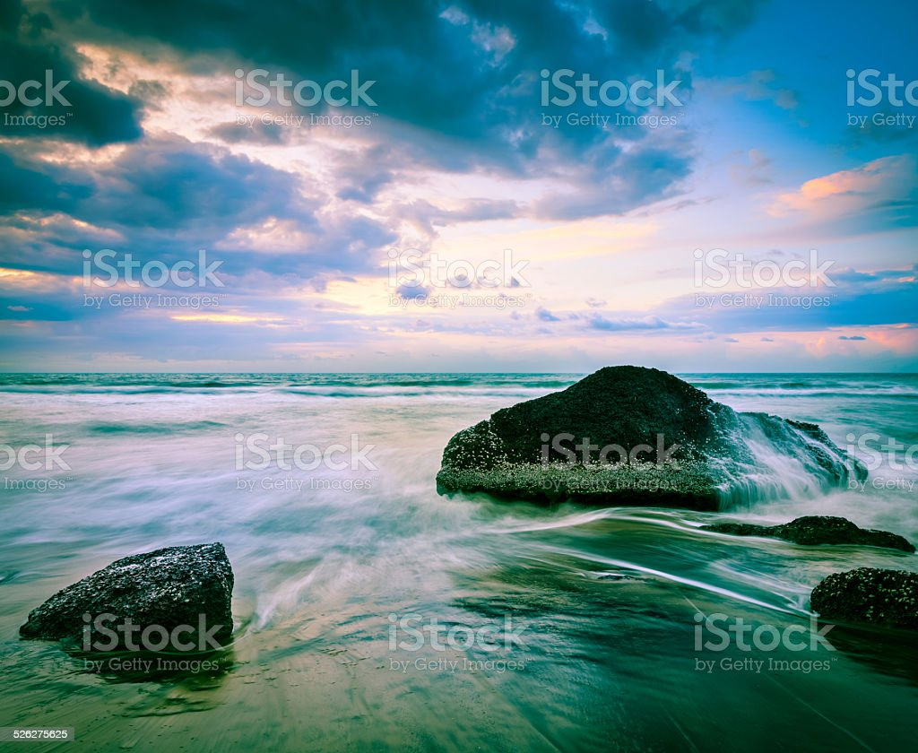 Waves and rocks on beach of sunset stock photo