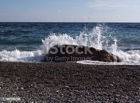 Waves and splashes of sea surf and stone on the seashore. Stones and shells on the beach.
