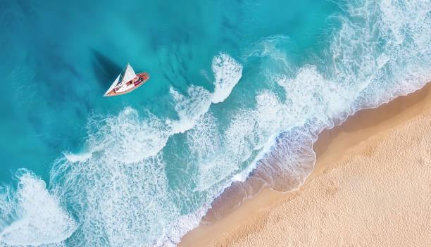 fale i jacht z góry. turkusowe tło wody z góry. letni pejzaż morski z powietrza. widok z góry z drona. obraz podróży - luksus zdjęcia i obrazy z banku zdjęć