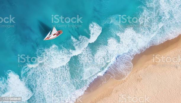 Photo of Waves and yacht from top view. Turquoise water background from top view. Summer seascape from air. Top view from drone. Travel-image