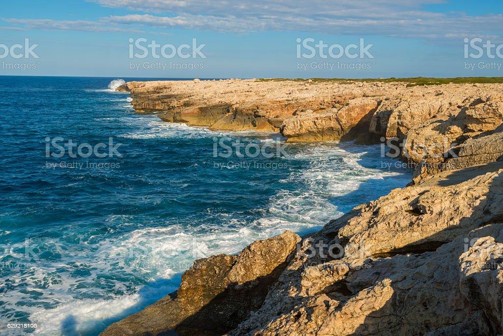 Waves are splashing around the rocky shore stock photo