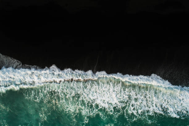 Waves at black sand beach. Black Sand beach and waves making interesting pattern. black sand stock pictures, royalty-free photos & images