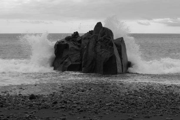 Waves breaking at the rock on the coast stock photo